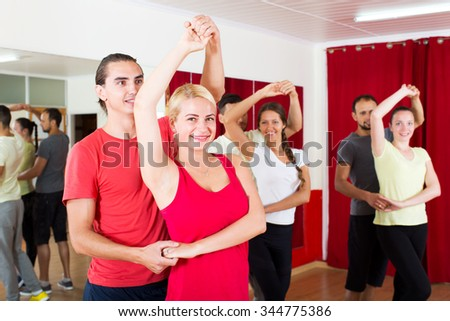 Cheerful couples dancing Latino dance in class