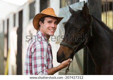 cheerful cowboy with a horse in stable - stock photo