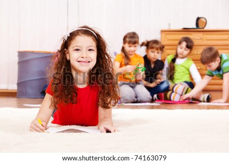 Cheerful curly girl laying on carpet with pencil - stock photo