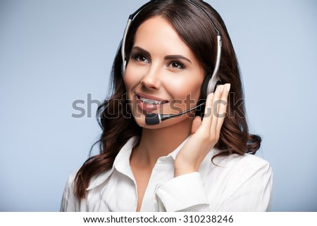 cheerful customer support female phone operator in headset, against grey background. Consulting and assistance service call center. - stock photo