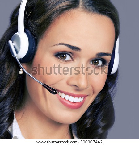 Cheerful customer support phone female operator in headset, posing at studio, over violet background - stock photo