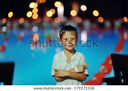 cheerful cute boy stands on a night the pool lights and reflection in water - stock photo