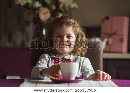 Cheerful cute girl sitting at the table - stock photo