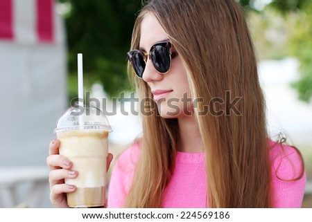 Cheerful cute hipster woman in the street cafe with Iced Latte coffee smiling - stock photo