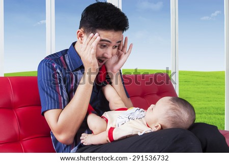 Cheerful dad sitting on sofa while playing peekaboo with his baby, shot at home - stock photo