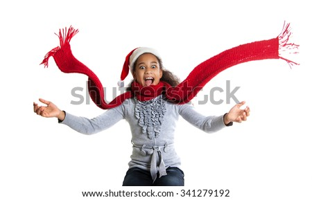 cheerful dark-skinned girl in a red scarf and hat of Santa Claus. Winter portrait of joyful adolescent girls - stock photo