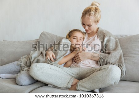 cheerful daughter sleeping on pregnant mother belly