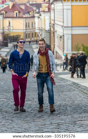 Cheerful day of twin brothers. Two stylish and handsome adult twin brothers are walking around and having fun together. Twins outdoor fashion style concept. - stock photo