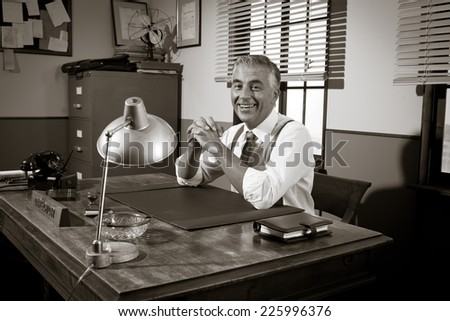 Cheerful director sitting at office desk, 1950s vintage office.