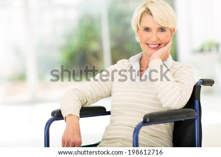 cheerful disabled senior woman in wheelchair - stock photo