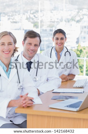 Cheerful doctors posing at their desk with x ray and a laptop computer - stock photo