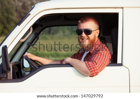 Cheerful driver of a small pickup truck - stock photo