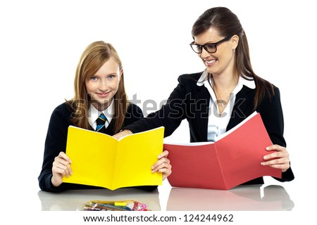 Cheerful educator sitting with a student and taking her through a lesson. Teacher student relationship. - stock photo