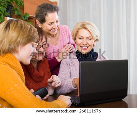 Cheerful elderly female friends browsing web on laptop at home