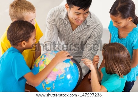 cheerful elementary school teacher with a globe teaching geography - stock photo