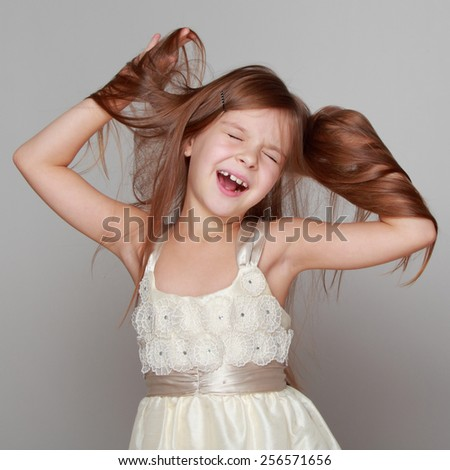 cheerful emotional little girl in a beautiful dress is dancing and having fun on a gray background - stock photo