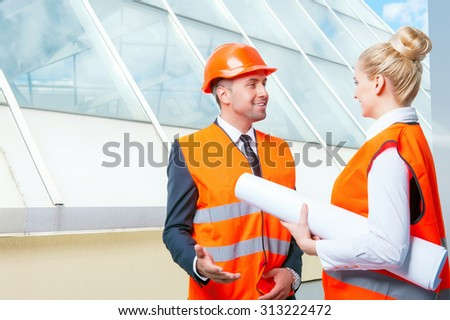 Cheerful engineers are discussing the plan of building with aspiration. They are looking at each other and smiling. The woman is carrying a blueprint. The man is standing in a helmet - stock photo