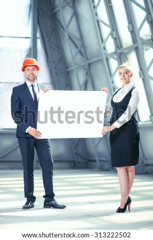 Cheerful engineers are standing and holding a blueprint. They are showing a white empty paper to the camera confidently. The workers are smiling and looking forward with joy - stock photo
