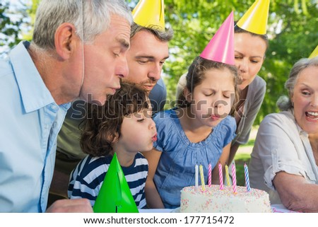 Cheerful extended family wearing party hats and blowing birthday cake in the park - stock photo