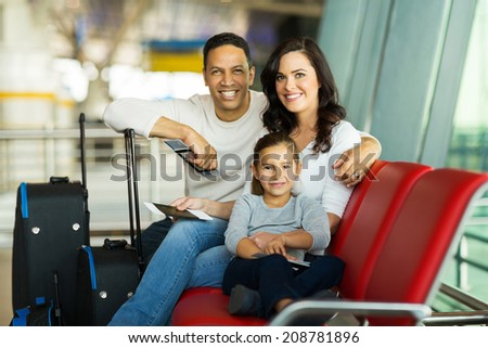 cheerful family at airport waiting for flight - stock photo