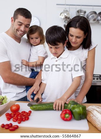 Cheerful family cooking together in the kitchen - stock photo