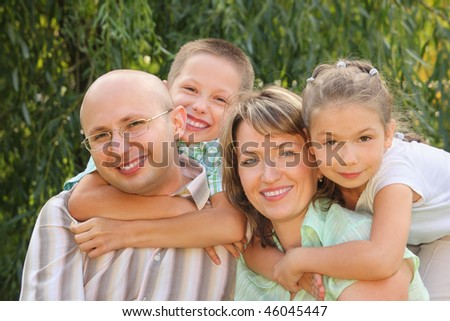 cheerful family. dad, mom, little boy and girl in early fall park. son is embracing father and daughter is embracing mother