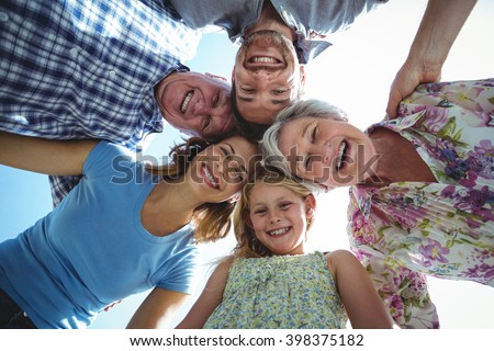 Cheerful family forming huddle in back yard against sky - stock photo