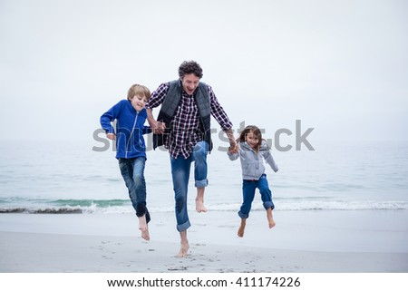 Cheerful family jumping at sea shore against clear sky - stock photo