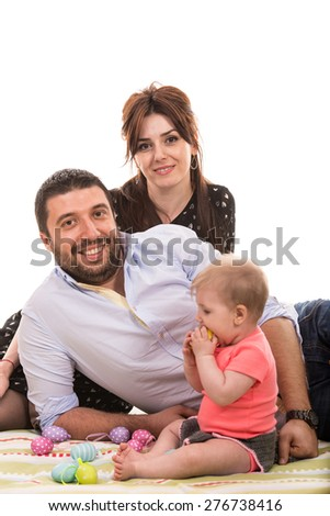 Cheerful family laying and their baby daughter playing with Easter eggs - stock photo