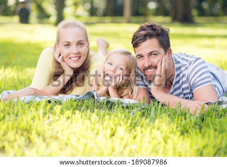 Cheerful family lying down in the park - stock photo