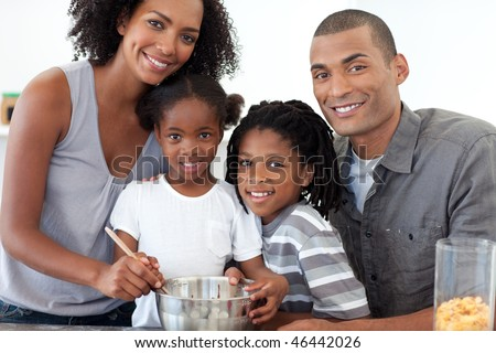Cheerful family making cookies together in the kitchen - stock photo