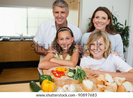 Cheerful family making sandwiches together - stock photo