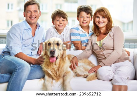 Cheerful family of four and their cute dog
