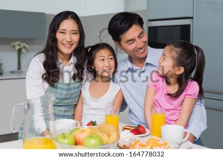Cheerful family of four enjoying healthy breakfast in the kitchen at home - stock photo