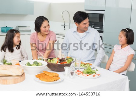 Cheerful family of four enjoying healthy meal in the kitchen at home