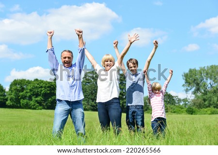 Cheerful family of four lifting arms up in the air - stock photo
