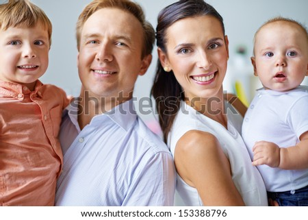 Cheerful family of four looking at camera with smiles
