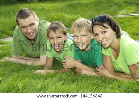 cheerful family of four lying on the grass in the park