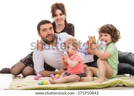 Cheerful family of four members with easter eggs against white background - stock photo