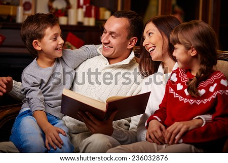 Cheerful family of four reading together at home - stock photo