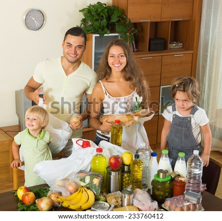 Cheerful family of four with bags of food at apartment