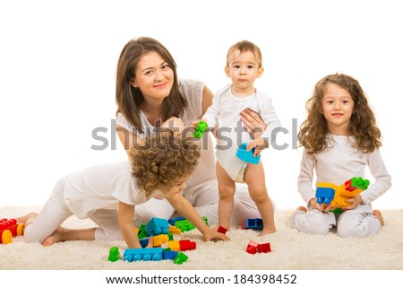 Cheerful family of mother and three kids sitting on carpet with toys