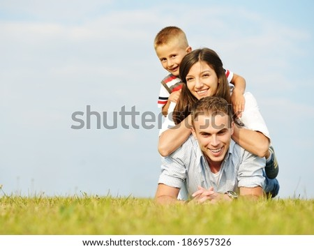 Cheerful family on beautiful summer meadow enjoying and having fun - stock photo
