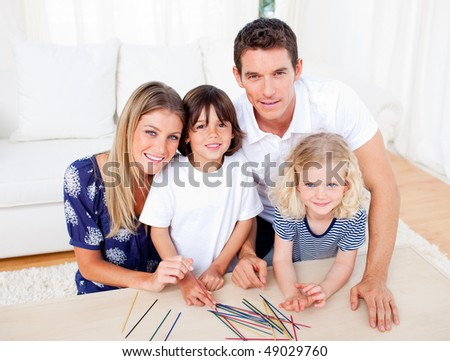 Cheerful family playing mikado in the living room at home - stock photo