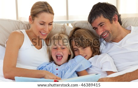 Cheerful family reading a book  lying on bed