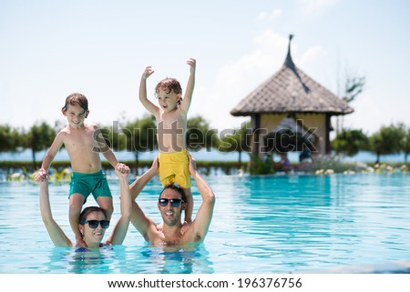 Cheerful family spending time in the swimming pool - stock photo