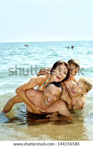 cheerful family swim in the sea together - stock photo