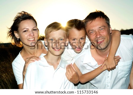 Cheerful family to watch the sunset together - stock photo
