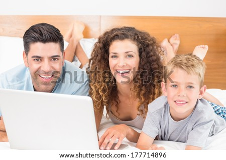 Cheerful family using laptop together on bed at home in bedroom - stock photo