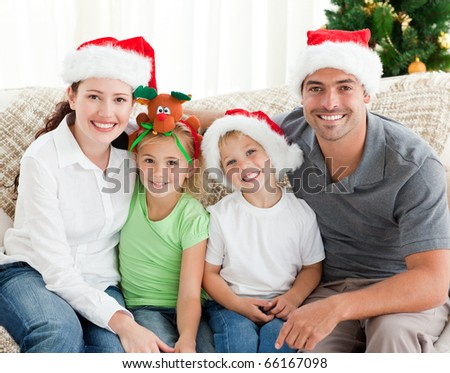 Cheerful family with Christmas hats sitting on the sofa at home